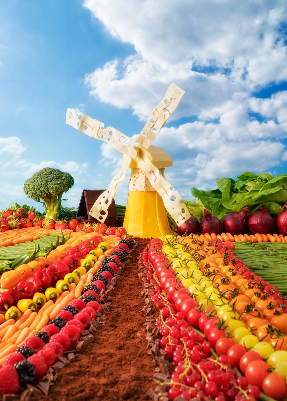 A dutch landscape with windmill made out of cheese, fruit, vegetables and cocoa