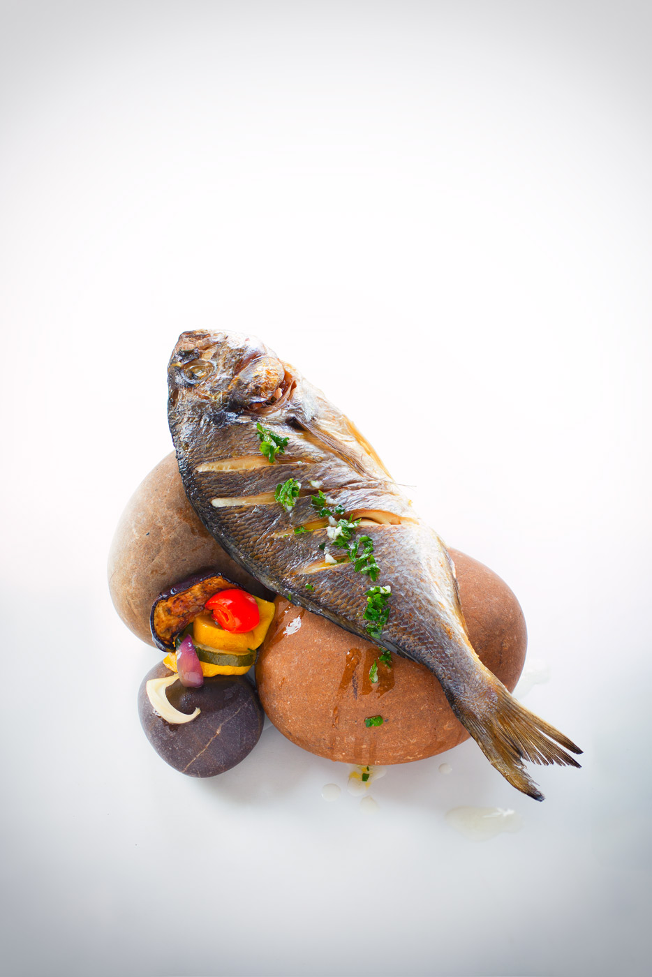 Recipe image depicting a grilled fish with vegetables displayed on stones
